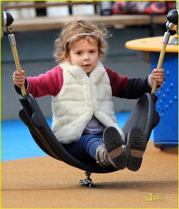 Honor Marie Warren plays on a swing and playground in NYC